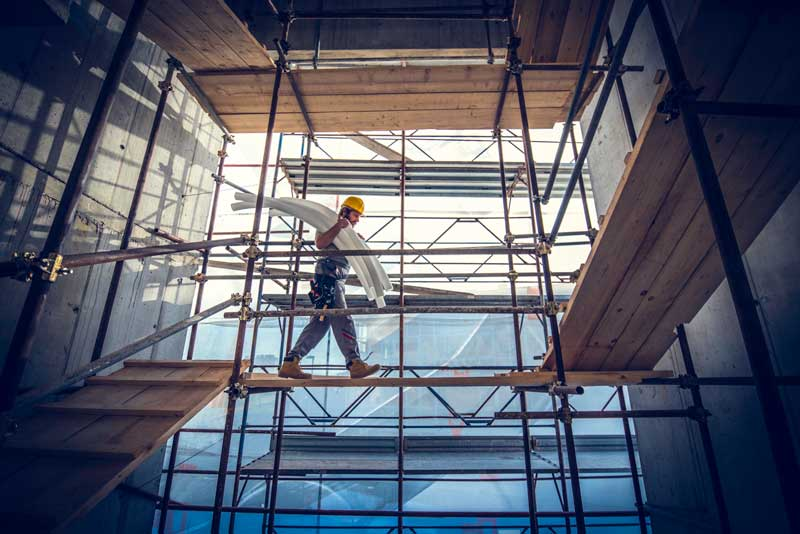 A construction worker carrying supplies while walking on scaffolding